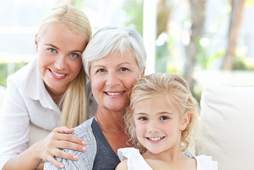 Elderly woman sitting between her blonde daughter and blonde granddaughter smiling